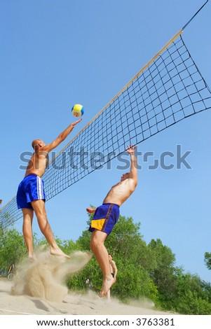 Three men playing beach volleyball - balding man strikes ball over net. Shot near Dnieper river, Ukraine. - stock photo