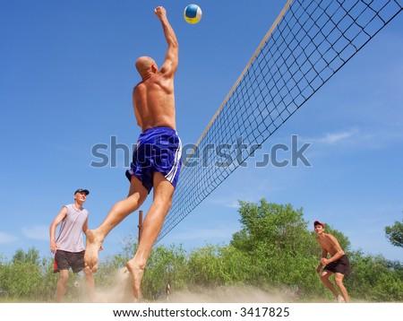 Three men playing beach volleyball - balding man strikes ball with fist. Shot near Dnieper river, Ukraine. - stock photo