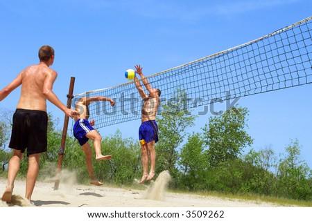 Three men playing beach volleyball - battle near net. Shot near Dnieper river, Ukraine. - stock photo
