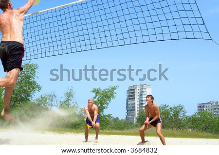 Three men playing beach volleyball - tall guy spikes, two others defend. Shot near Dnieper river, Ukraine. - stock photo