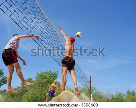 Three men playing beach volleyball - teenager blocks a tall guy over net. Shot near Dnieper river, Ukraine. - stock photo
