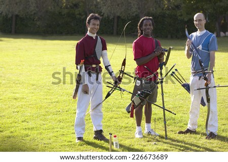 Three men preparing their bows and arrows for an archery contest