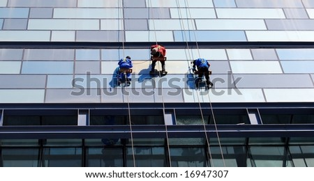 Three men repairing the wall of the skyscraper