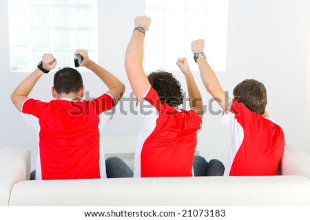 Three men sitting on couch with hands up. Rear view. - stock photo