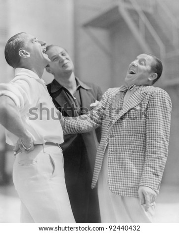 Three men standing together and laughing - stock photo