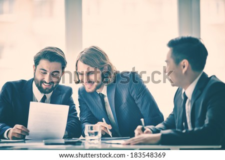 Three men talking in board room - stock photo