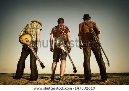 Three men with guitars on the river.   - stock photo