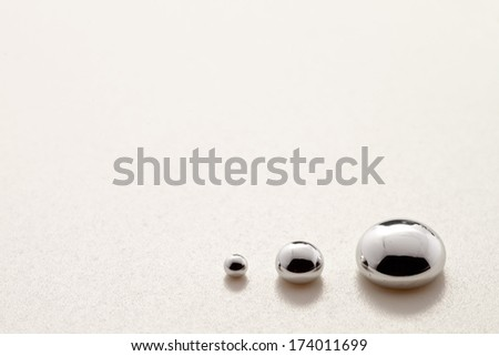 Three mercury drops over a shiny plastic surface - stock photo