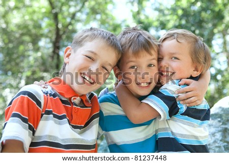 Three merry brothers hugging, in park - stock photo