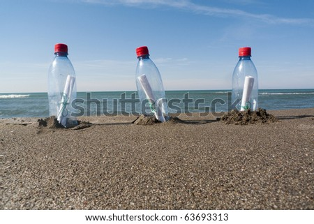three messages in three plastic bottles - stock photo