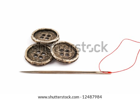 Three metal buttons and needle isolated on white