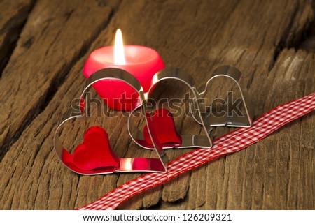 Three metal heart shapes and a candle with a red and white checkered deco ribbon on a old wooden board - stock photo