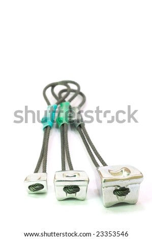 Three metal nuts / chocks used as protection when rock climbing - stock photo