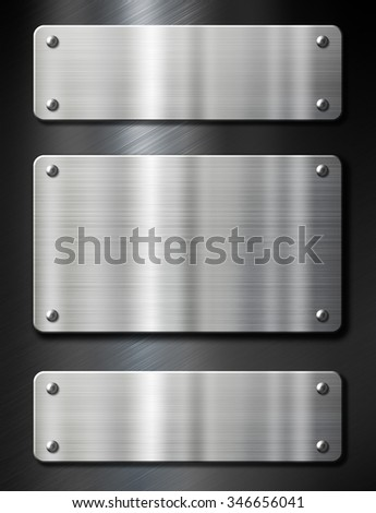 three metal plates on black brushed background - stock photo