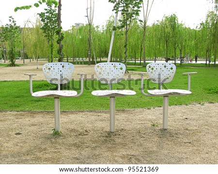Three metallic design chairs in a park in Barcelona - stock photo