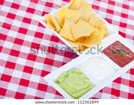 Three Mexican dips and tortilla chips - stock photo