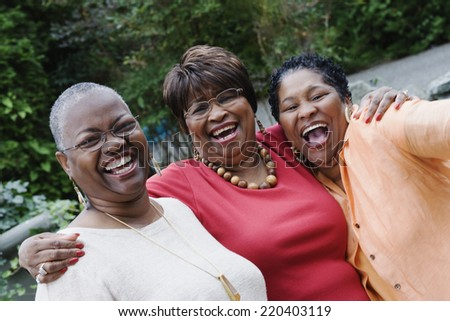 Three middle-aged African women smiling and hugging - stock photo
