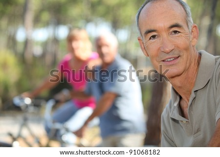 Three middle-aged people on bike ride - stock photo