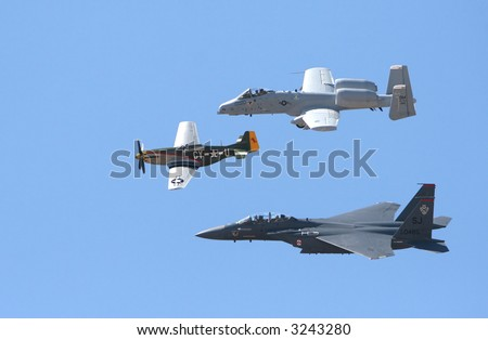 Three military aircraft flying through a blue sky