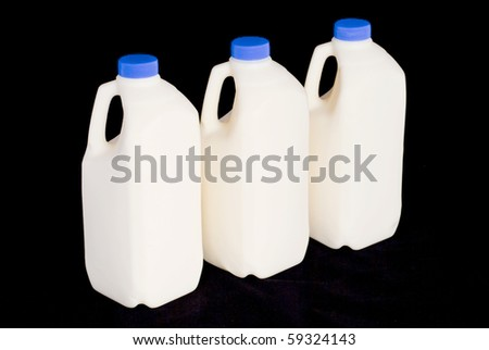 Three milk bottles on a black background