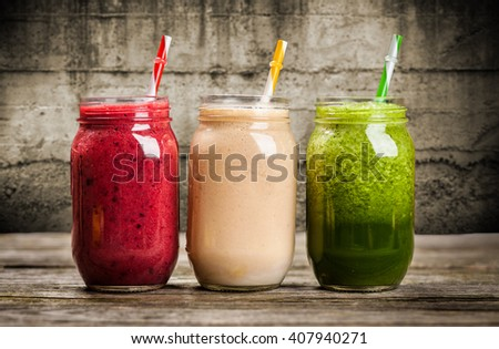Three milkshakes and smoothies on wooden table - stock photo