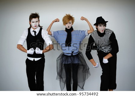 three mime actors in action - stock photo