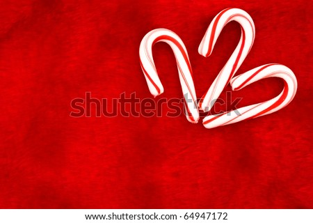 Three mini candy canes on a red textured background, Christmas Time - stock photo