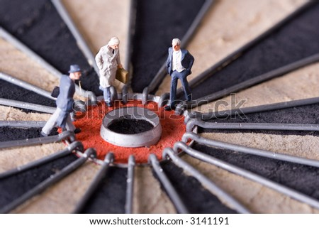 Three miniature businessman walking to the center of a dartboard. Shallow depth of field. - stock photo