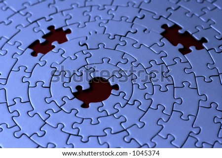 three missing pieces in a blue jigsaw - focus is on the center hole