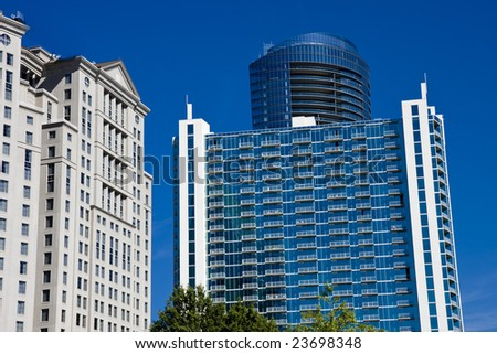 Three modern buildings rising against a deep blue sky