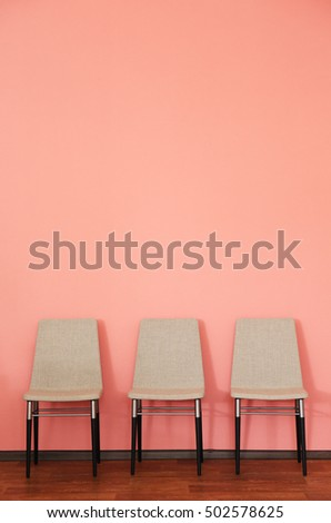 Three modern chairs on wall background