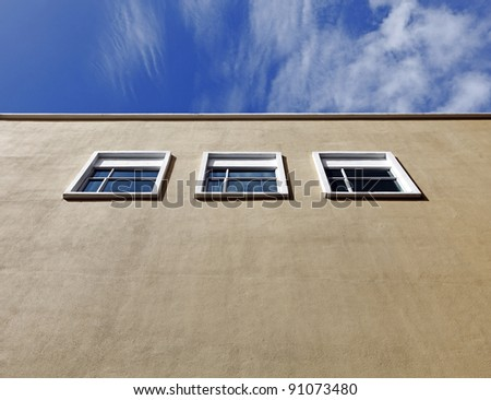 Three modern window frames on a blank grungy brown concrete wall under a blue sky with clouds. - stock photo