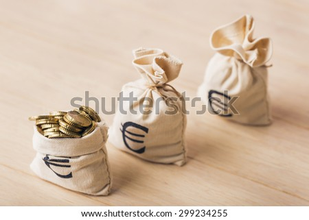 Three money bags with euro coins, selected focus - stock photo
