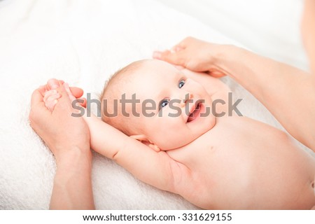 Three month baby girl is receiving arm massage from a female massage therapist