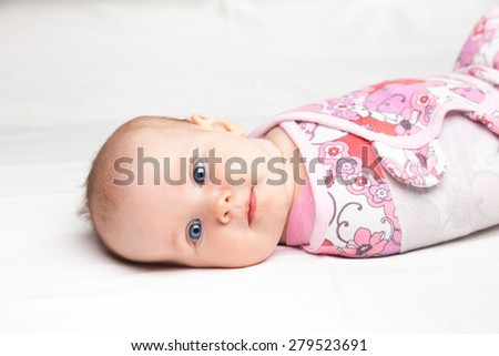 Three month baby girl wrapped in a modern winged baby swaddle laying on a bed. Swaddling is a practice of wrapping infants in cloths in order to prevent limb movement