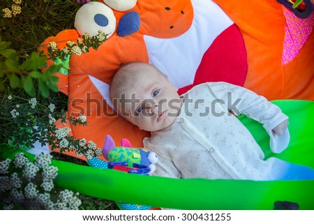 Three-month baby lying on the carpet bright children in the yard. - stock photo