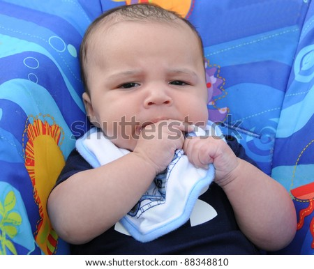 Three Month Old Baby Boy Chewing on Bib Looking at Camera - stock photo