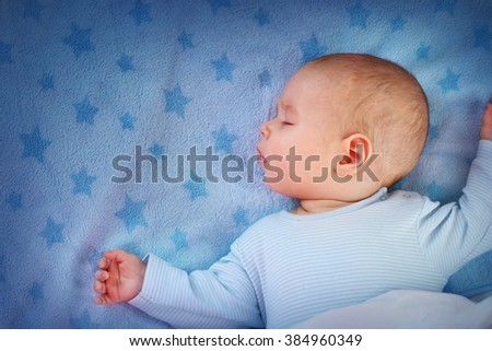 three month old baby sleeping on blue blanket - stock photo