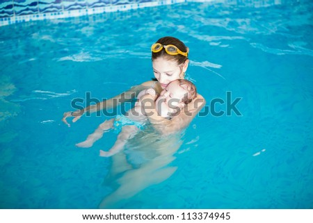 Three months baby relaxing in the swimming pool with mother - stock photo