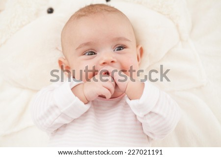 Three months old baby girl lying on a blanket. - stock photo