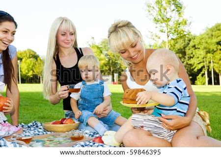 Three mother with kids having picnic - stock photo