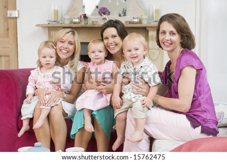 Three mothers in living room with babies smiling - stock photo