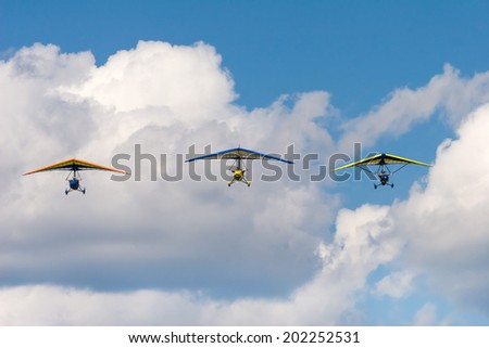 Three motor hang gliders in a formation against the cloudy sky. - stock photo