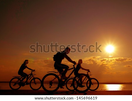 three mountain biker silhouette in sunrise  against sun set cloudy skr Copy space for inscription