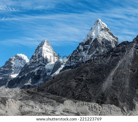 Three mountain peaks Nirekha (6169 m), Kangchung (6062 m), and Chola (6069 m) in the area of Cho Oyu - Gokyo region, Nepal, Himalayas - stock photo