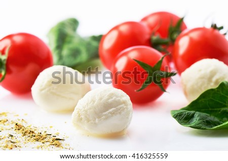 three mozzarella cheese balls, five ripe cherry tomatoes, greens and spices on the white background. horizontal format - stock photo