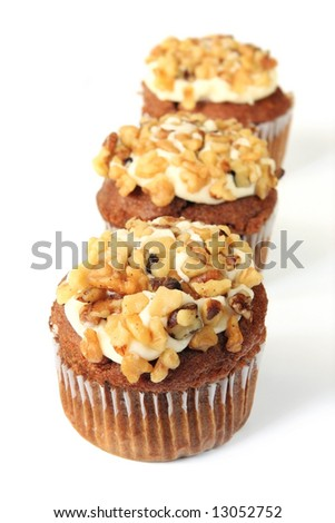 Three muffins topped with cream cheese frosting and walnuts.  Shallow depth of field, with focus on front muffin.