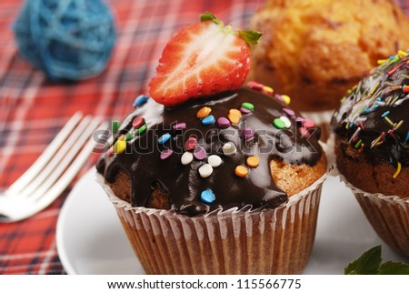 Three muffins with sprinkles on the plate closeup - stock photo