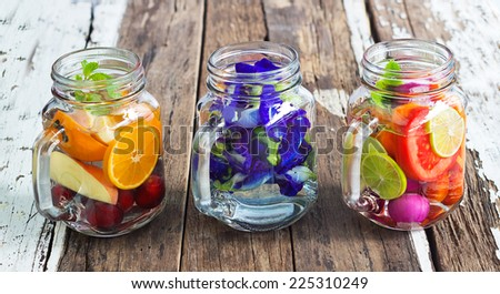 Three mug delicious refreshing drink of mix fruits and herb on wooden - stock photo