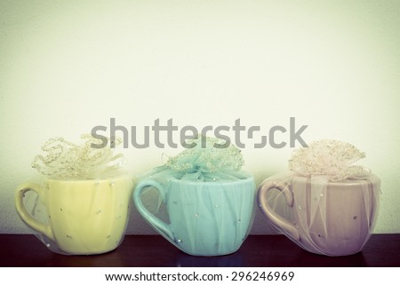 Three mug on wooden table over grunge background. Colorful stack coffee cups on wood board. Vintage retro effect style pictures. - stock photo